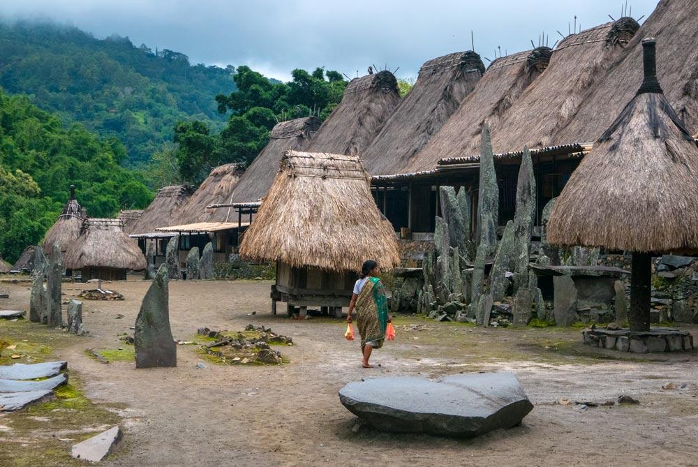 Casa tradicionales de Bajawa. Con su forma característica en punta a dos aguas. una señora pasea por el pueblo con ropas tradicionales.
