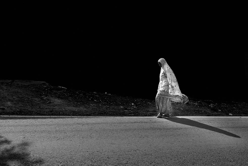 Mujer con velo camina por la cuneta sobre fondo negro. De Java a Bali en autostop.