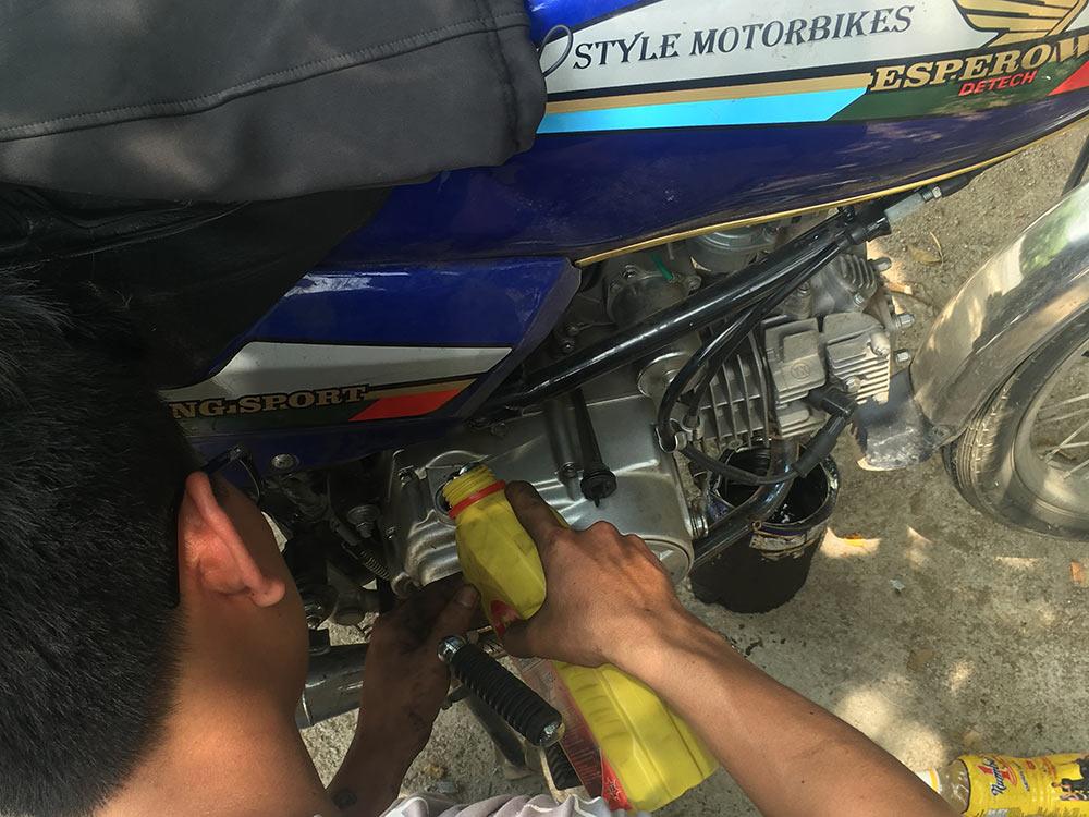 Un hombre le echa aceite a nuestra moto - Viajar en moto por Vietnam