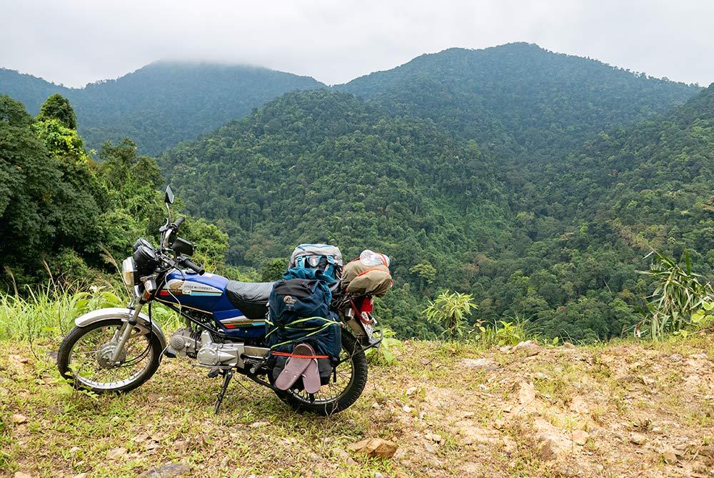 Honda detech con dos mochilas por cada lado amarradas con pulpos. En el fondo la masa forestal de una selva - Viajar en moto por Vietnam