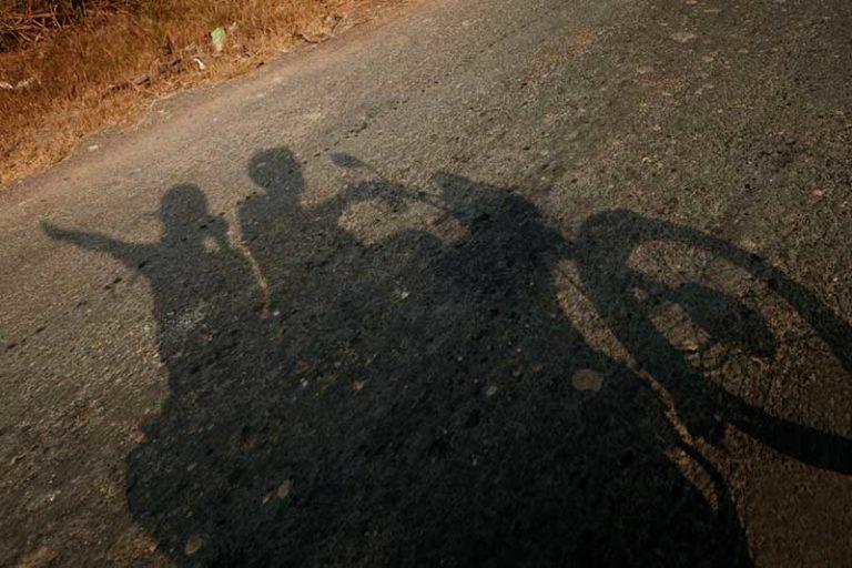 Silueta proyectada en la carretera de nostros dos levantado las manos. El sol estaba bajo y nuestras sombras se veían en la carretera.