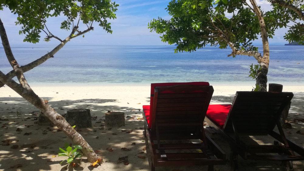 Tumbonas bajo la sombra en un playa paradisíaca.  Cómo conseguir hoteles barato.