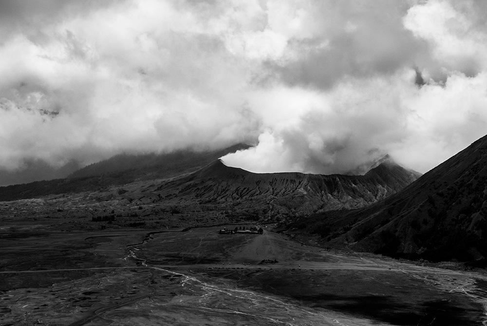 Volcan bromo visto desde la distancia de un mirador. El humo sale por el cono del volcán. Volcanes activos en el mundo.