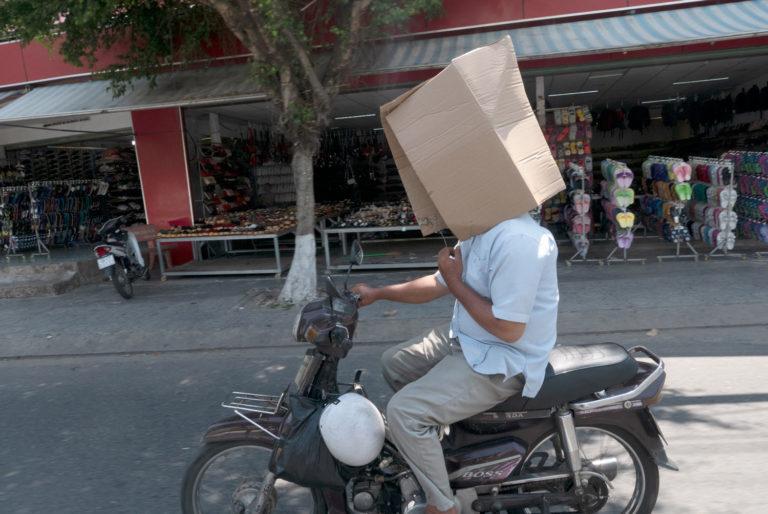 Un hombre conduce una moto en Asia con una caja en la cabeza para protegerse del sol. Motos en Asia