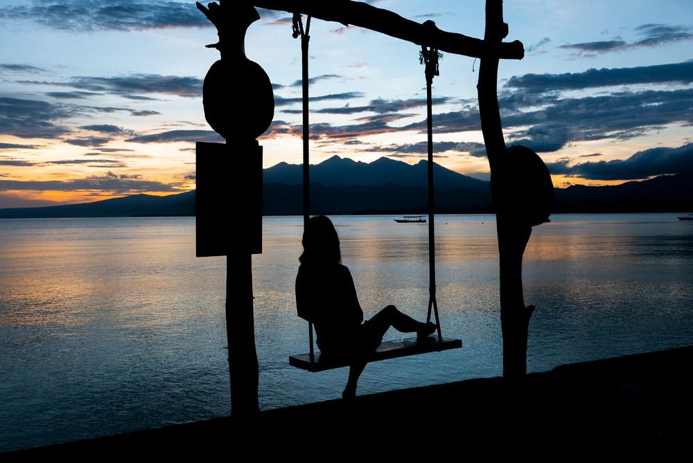 chica disfrutando de una puesta de sol en un lugar tranquilo y paradisíaco. Turismo sostenible. 7 pasos para viajar de forma sostenible. Perder el rumbo