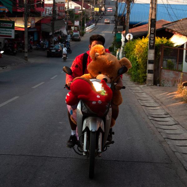 Un chico lleva un peluche gigante en su moto. Motos en Asia.
