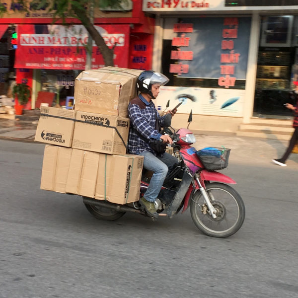 Un condusctor en una moto lleva varias cajas mientras escribo por teléfono. Motos en Asia.