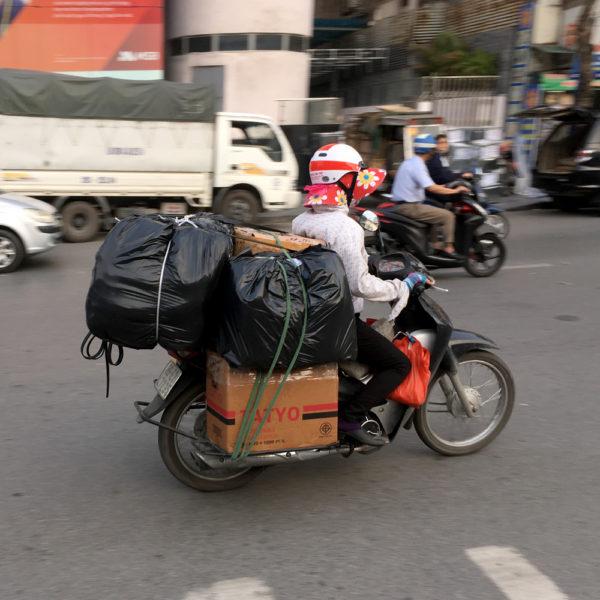 Una moto con cajas y bolsas en la parte de atrás. Motos en Asia.