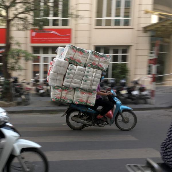 Una moto donde apenas se ve al conductor como muchas cajas. Motos en Asia.