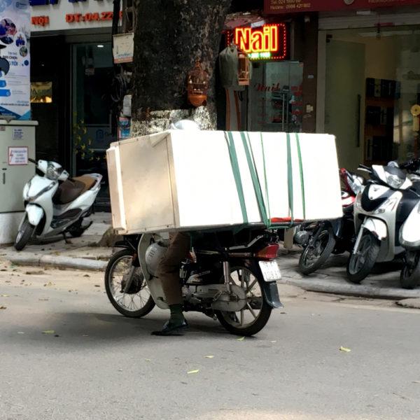 Una nevera en la parte de atrás de una moto. Motos en Asia.