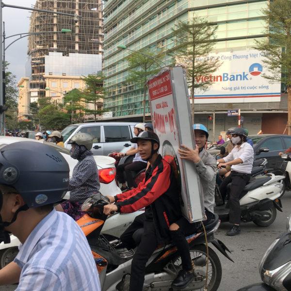 Dos chicos en moto el de atrás lleva un letrero de grandes dimensiones entre los dos. Motos en Asia.
