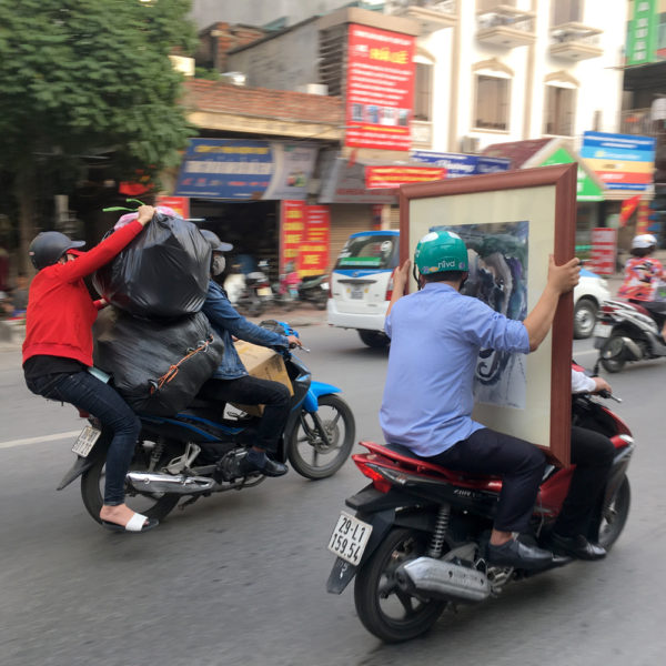Dos motos. Una lleva a dos personas y una de ellas lleva un cuadro que tapa por completo al conductor.Parece que va llevando el cuadro un solo conductor sin ver la carretera. La otra moto lleba a una señora de copiloto con dos bolsas tan grandes que está a punto de caer de la moto. Motos en Asia.