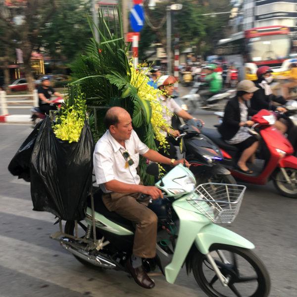 Un hombre lleva en su moto varias coronas de funeral. Motos en Asia.