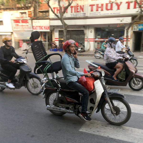 Un chico lleva una silla de oficina en la moto mientras habla por teléfono. Motos en Asia.
