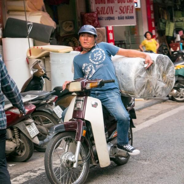 Un chico esta esperando en una acera y en la parte de atrás de la moto dos rollos de moqueta. Motos en Asia.