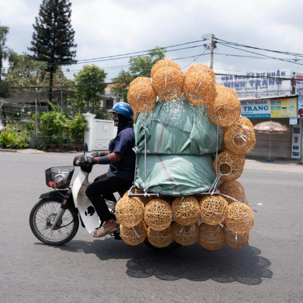 Una moto llena de lamparas. El conductor apenas cabe en el sillín. Motos en Asia.