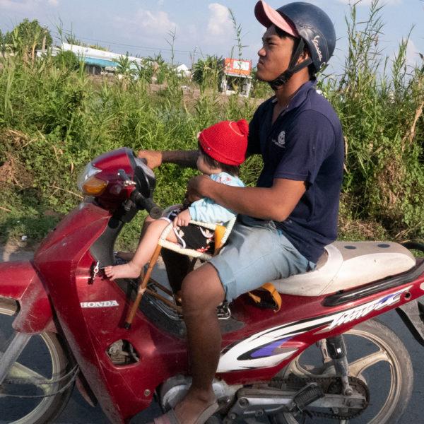 Un niño va con su padre en una moto. Este va sentado en una silla de madera entre el conductor y el manillar. Motos en Asia.