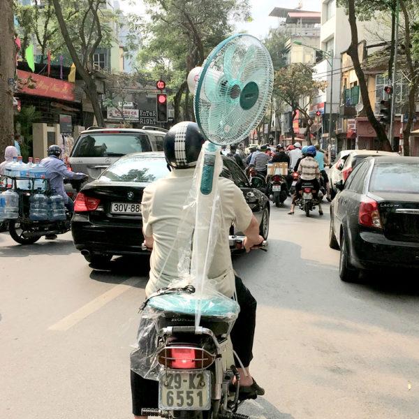 Un conductor lleva un ventilador en vertical en la moto. Motos en Asia.