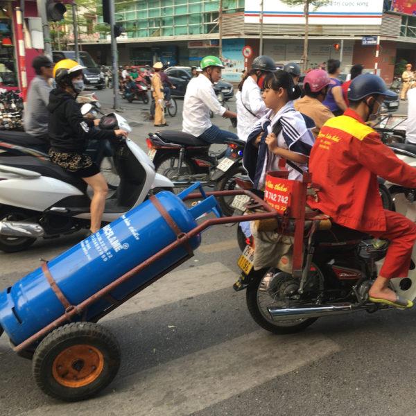 Una moto lleva enganchado un remolque con una gran botella de gas. Motos en Asia.