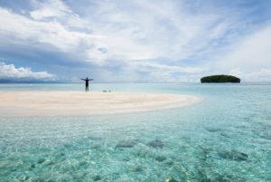 Una persona alza los brazos en cruz en medio de una islote de arena rodeado de un mar turquesa. RAJA AMPAT. PAPÚA. INDONESIA