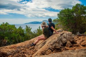 Una pareja sentados en una piedra rodeada de pinos observa el golfo de Orosei en un día soleado. Enfrente el mar. Perder el Rumbo