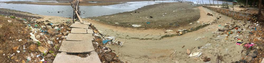 Playa llena de basura. un montón de plásticos por todo el lugar.