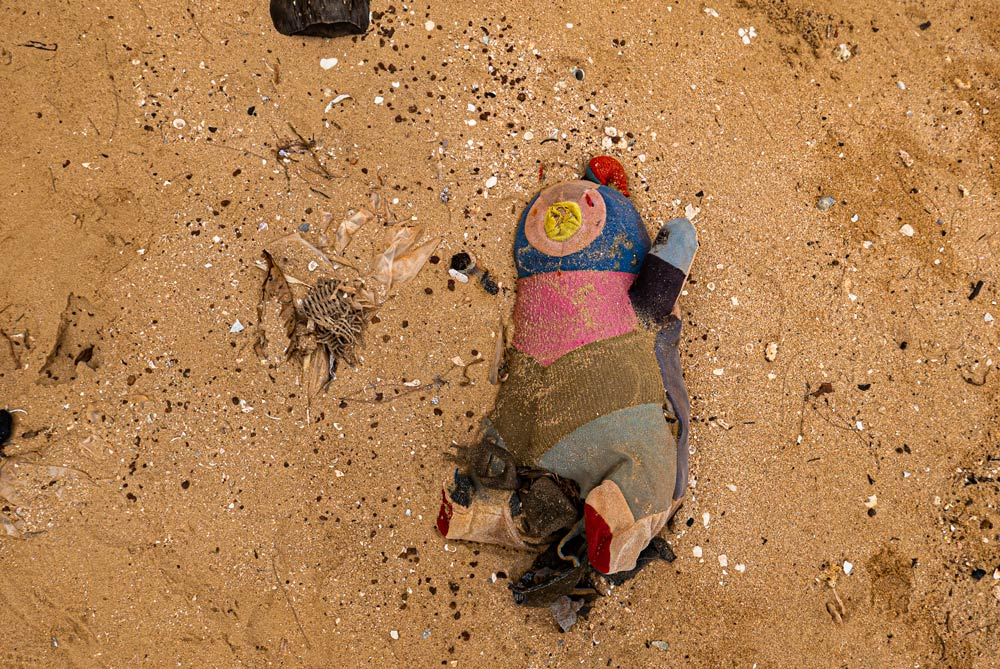 Primer plano de un muñeco de trapo tirado en la arena de la playa como residuo o basura. Phu Quoc
