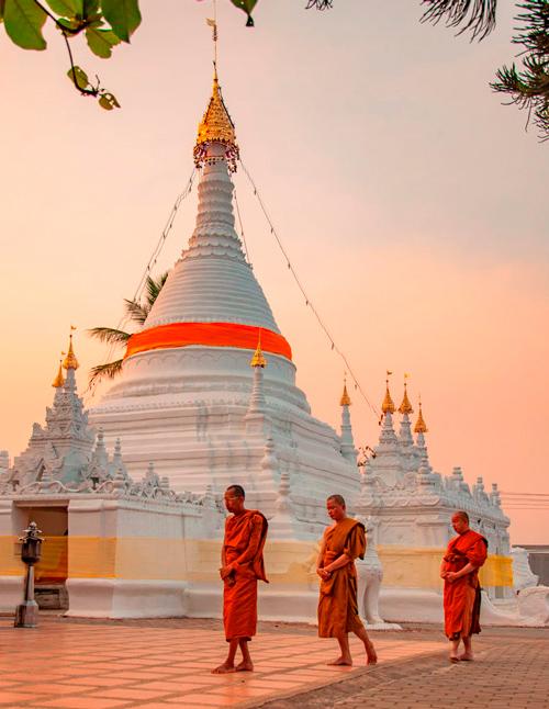 Grupo de monjes lanzan sus oraciones mientras rodean un templo. Van de naranja. De fondo con el cielo naranja de la puesta de sol vemos un templo de blanco reluciente.