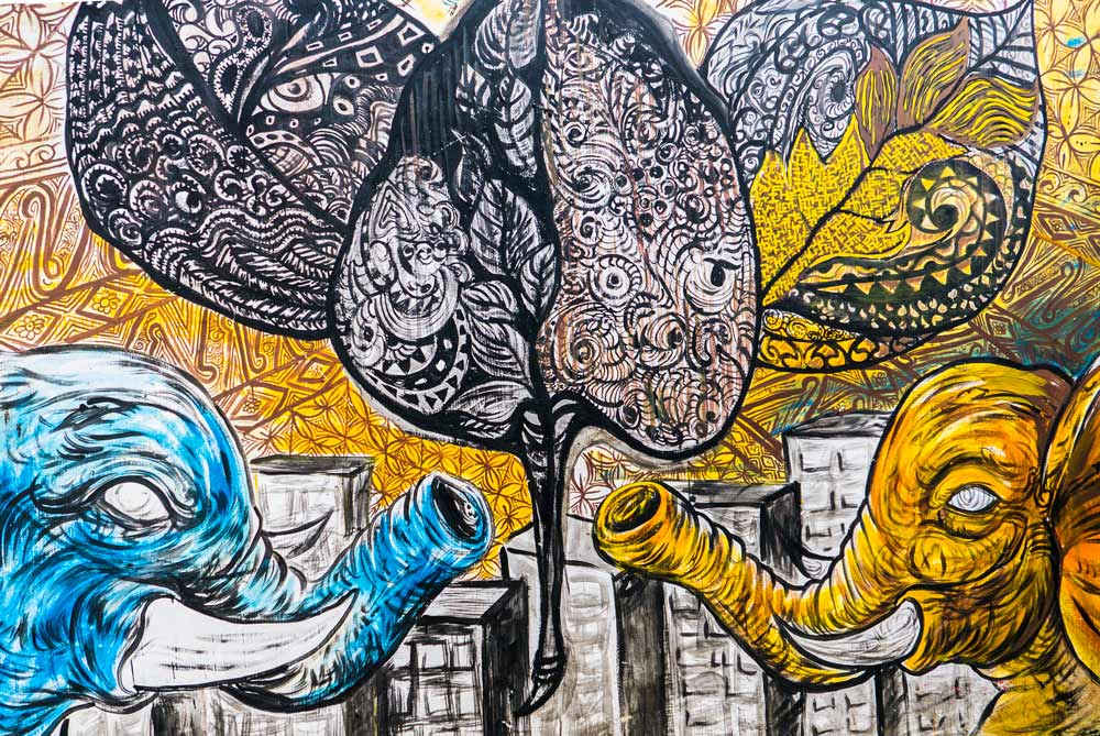 Pintura étnica de dos elefantes en una pared. Se mexclan axzules, amarillos y negros. Yogyakarta