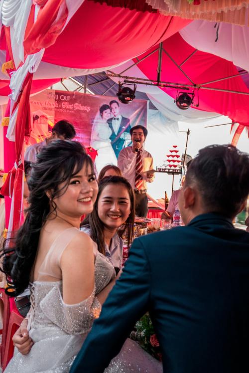 En una boda la novia sonríe a la cámara. Tiene una larga melena negra y rizada. Al fondo se ve el un cartel con una foto de los novios y un señor cantando en el típico karaoke vietnamita. Islas Cham