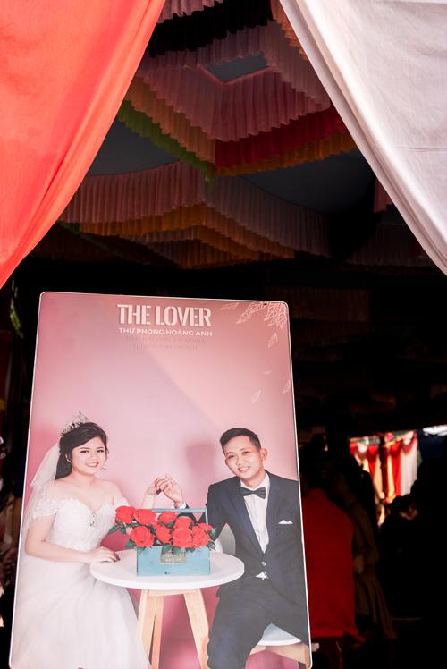 Cartel de la boda donde podemos ver a los novios sentados alrededor de una mesa blanca con flores rojas. En el cartel está escrito The Lover. Islas Cham