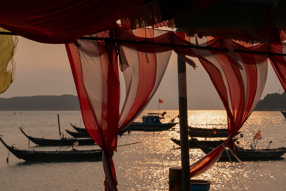Telas al viento de la carpa de una boda. Entre las telas se ve el mar y los barcos de los pescadores vietnamitas. Islas Cham