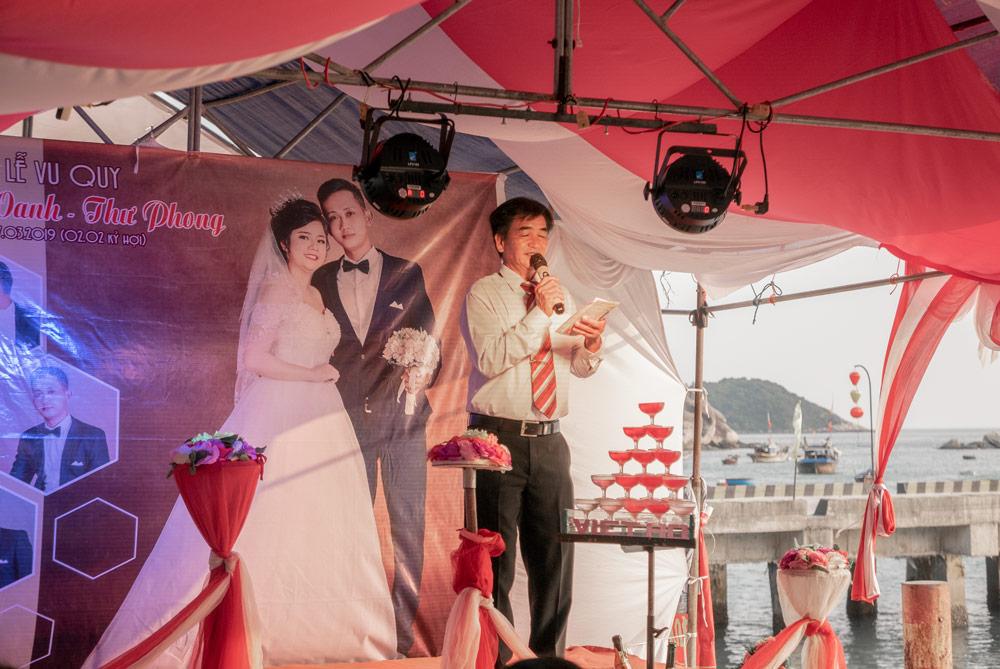 Boda vietnamita. Cartel de los novios de fondo en un escenario dedicado al karaoke. Vemos a un señor cantando. Islas Cham