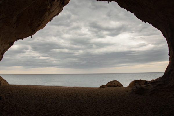 Entrada a la cueva de Cala Luna vista desde dentro de la gruta. Se ve el mar al fondo. La cueva tiene arena en su base. Golfo de Orosei. Cerdeña