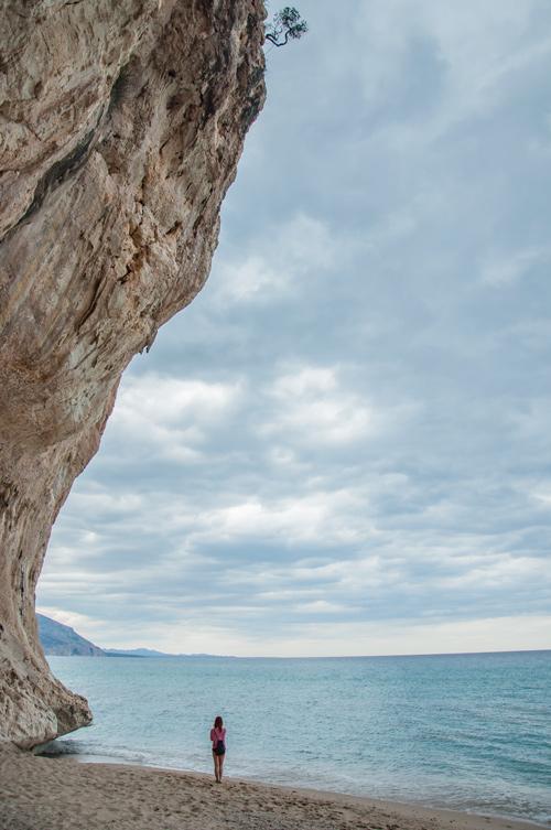 Chica el fondo en una playa. Parece muy pequeña debido a la inmensa roca que tiene a su izquierda y que se eleva hasta el infinito. Golfo de Orosei. Cerdeña