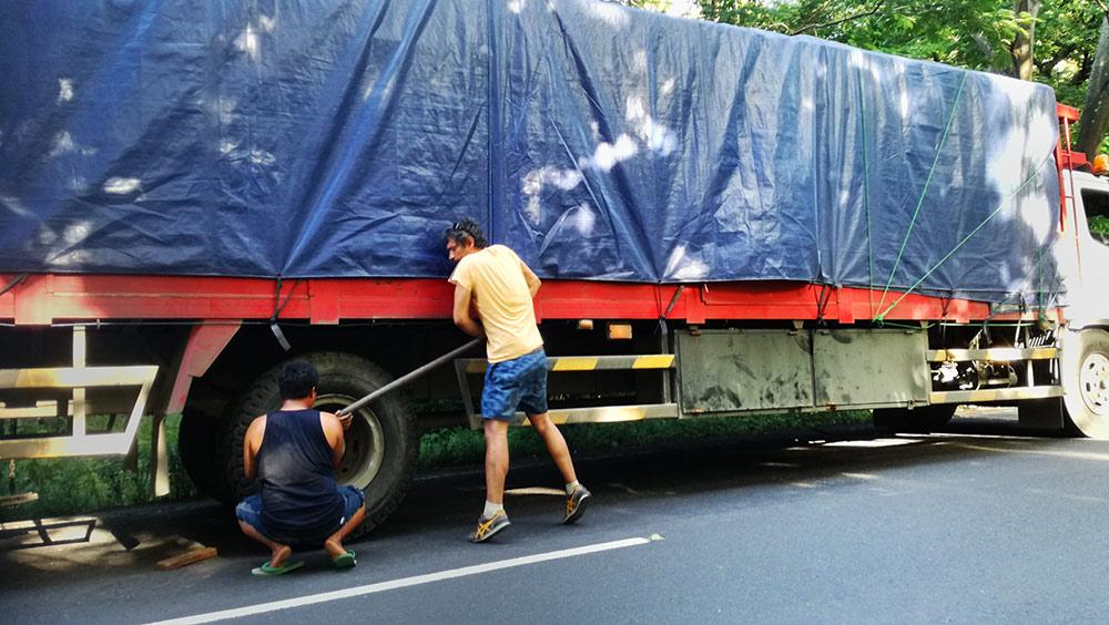 Un camión pinchado en la cuneta mientras dos chicos intentan desaflojar una rueda.