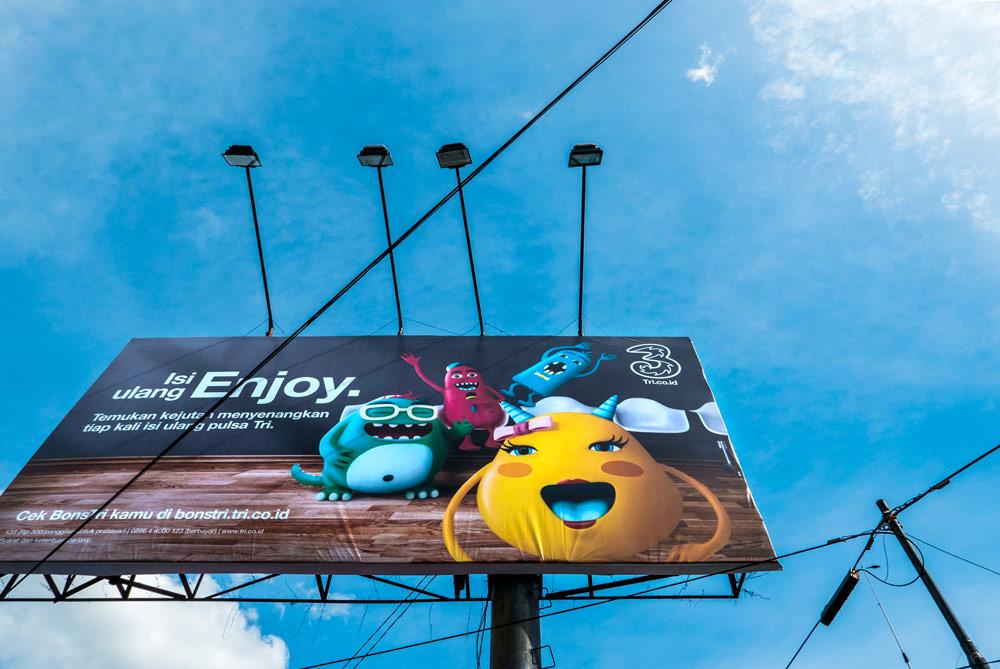 Cartel colorido de dibujos animados visto desde el suelo. Se ve el cartel y el cielo azul. Yogyakarta