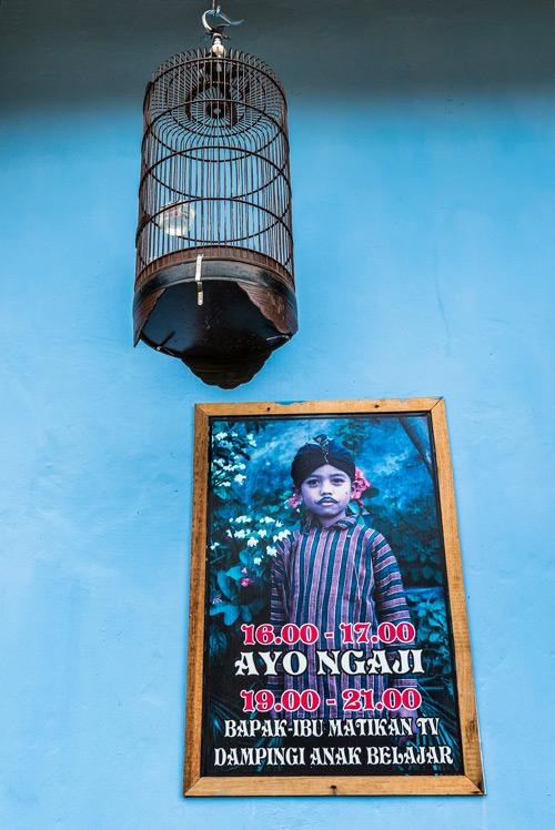 Cartel donde aparece un niño musulmán y una jaula de pajaritos colgados en la pared azul de una de las casas de colores del río Code. Yogyakarta