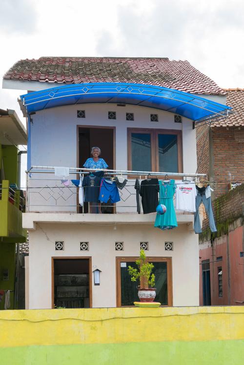 Señora sonriente asomada a la ventana de una de las casas del Río Code. Yogyakarta