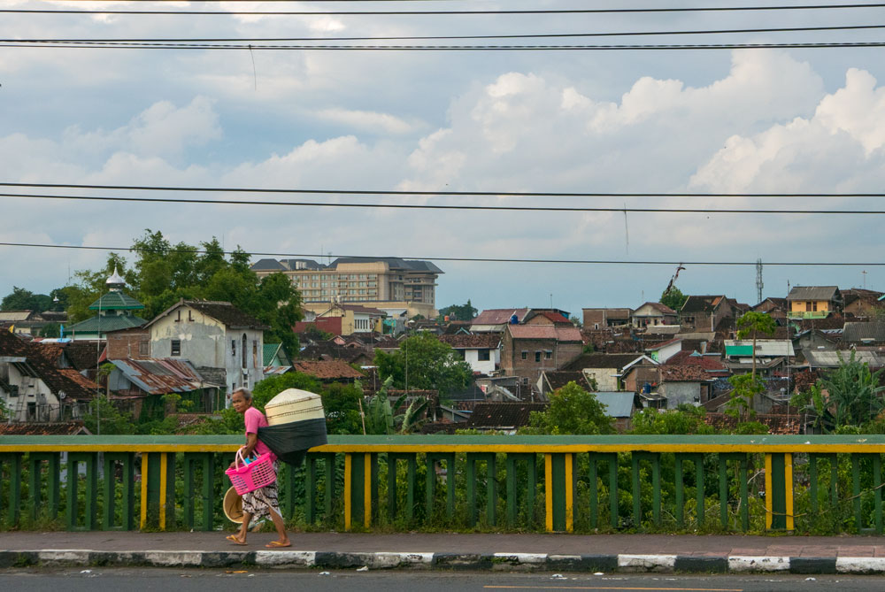 Mujer vestida de un color rosa intenso cruza el Puente de Gandolaya cargada con tres cestos. Yogyakarta