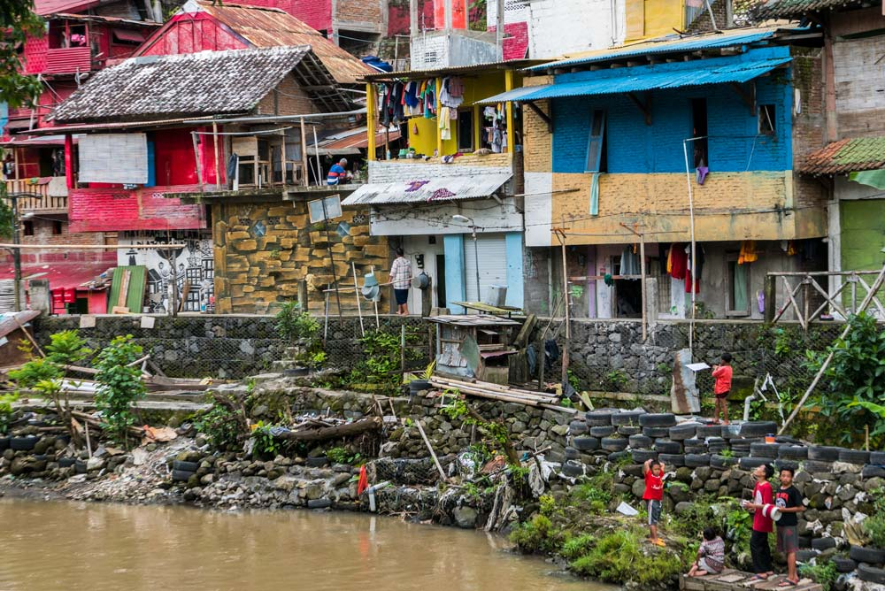 Casitas de colores, rojos, azules. Son casas humildes a orillas del río donde juegan varios niños. Yogyakarta
