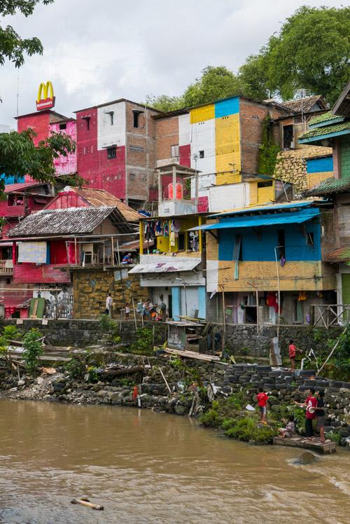 Contraste entre las humildes casas de colores del río Code y un cartel del McDonalds que está en lo alto. Yogyakarta