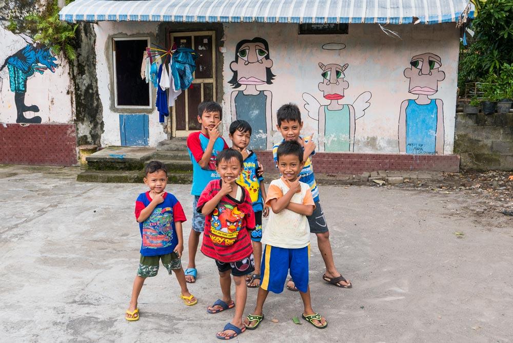 6 niños posando para la fotografía. Al fondo se ve una casa adornada con pinturas de arte callejero. Yogyakarta