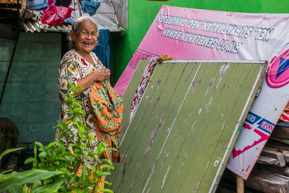 Retrato de una anciana muy sonriente y vestida con un vestido de flores de colores. Yogyakarta