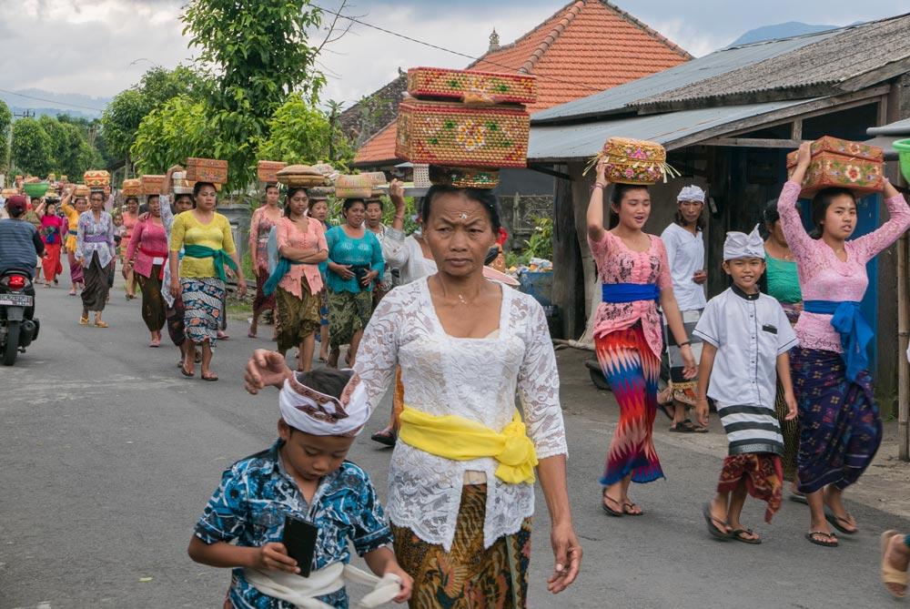 Balineses caminando con cestos llenos de ofrendas hacia el templo