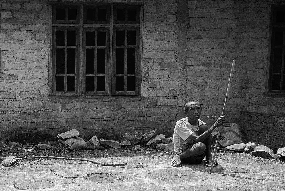 Un señor sentado en la cuneta observa a la gente pasar.