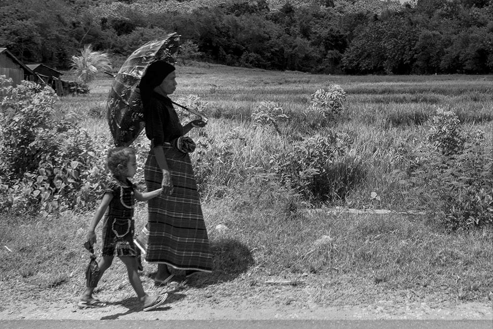 Una señora con paraguas para taparse del sol lleva a us hija cogida de la mano por las cuneta.