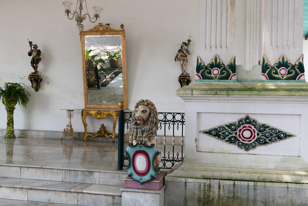 Detalles del Palacio del sultán. Un león desculpido sobre una pequeña columna y un espejo de marco dorado al fondo. Yogyakarta
