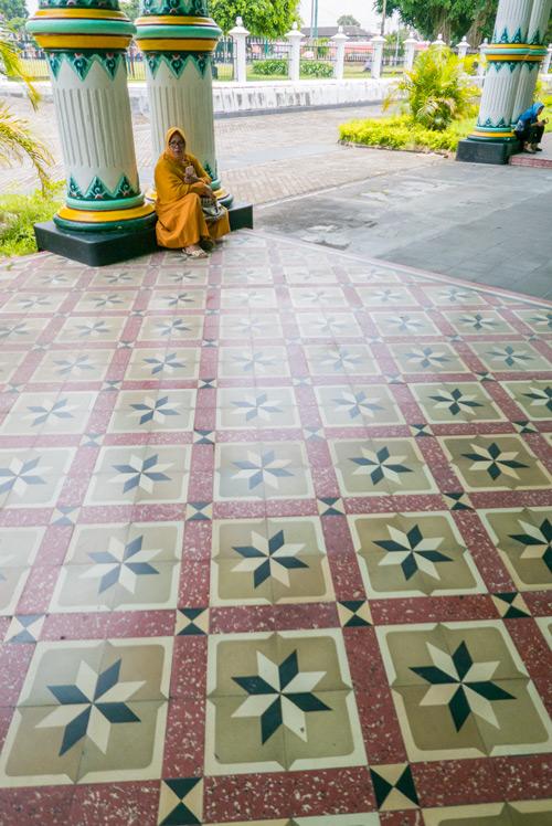 Suelos del palacio del sultán con bellos dibujos y una señora sentada en unas columnas al fondo. Yogyakarta