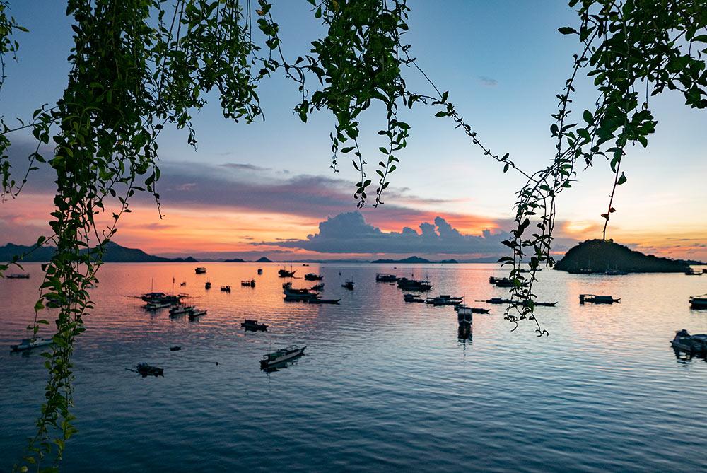 Puerto al atardecer en Labuan Bajo. La puesta es de colores cálidos rojizos.